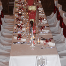 StuhlHussenWorld weisse Stuhlhussen mit Bordeauxroten Schleifen und roter Tischdekoration